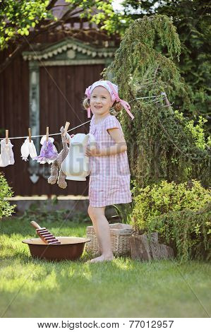 Cute child girl playing toy wash in summer garden