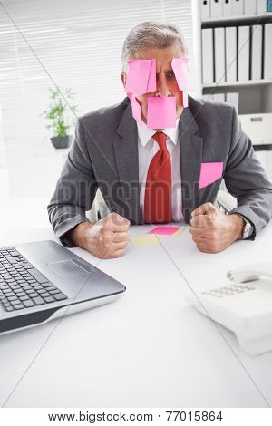 Overwhelmed businessman with sticky notes on head in his office