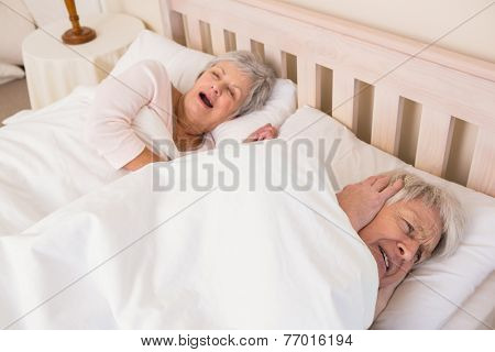 Senior man blocking out his wifes snoring at home in bedroom