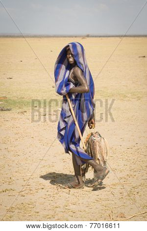 Boy Carries The Dried Fishes From The Lake Turkana, Kenya