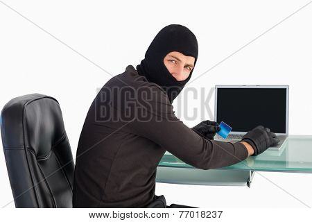 Burglar shopping online with laptop while looking at camera on white background
