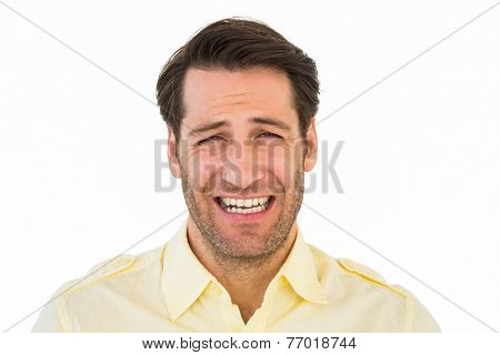 Desperate handsome man frowning at camera on white background