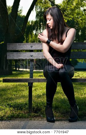 Beautiful Young Brunette On Bench Fashion Portrait