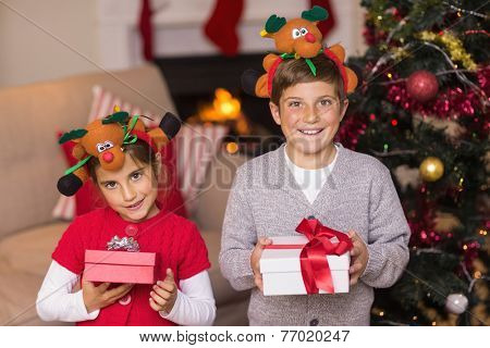 Brother and sister in headband holding gift at home in the living room