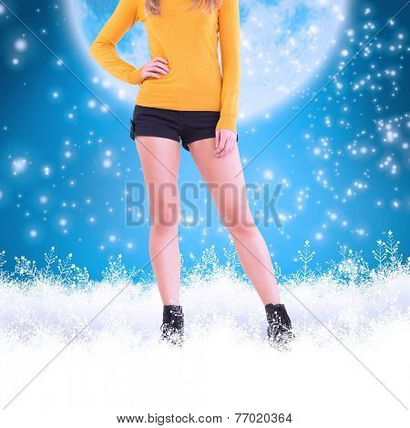 Lower half of woman in boots and shorts against blue background with vignette