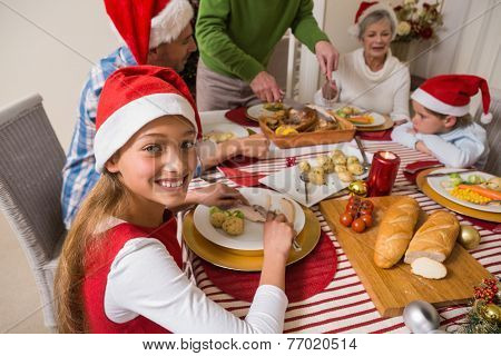 Portrait of cute girl in santa hat during christmas dinner at home in the living room