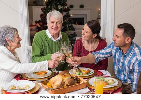 Portrait of happy family toasting at christmas dinner at home in the living room