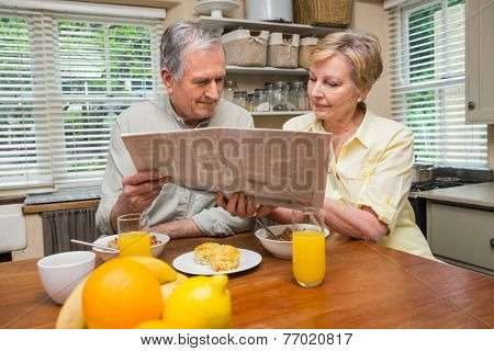 Senior couple having breakfast together at home in the kitchen