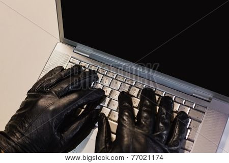 Close up of burglar hacking a laptop on black background