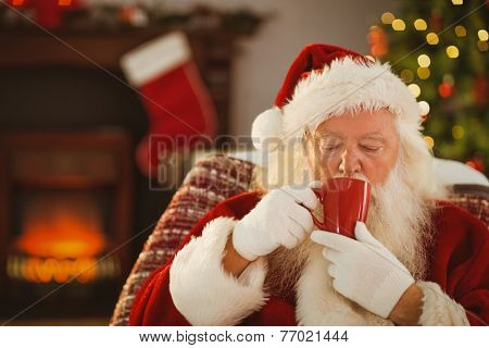 Father christmas drinking a hot beverage at home in the living room