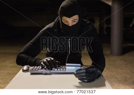 Burglar shopping online with laptop on black background
