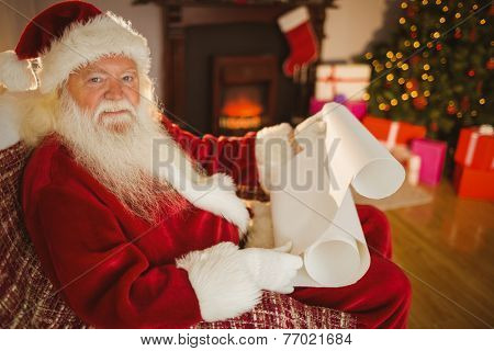 Smiling santa claus reading his list at home in the living room