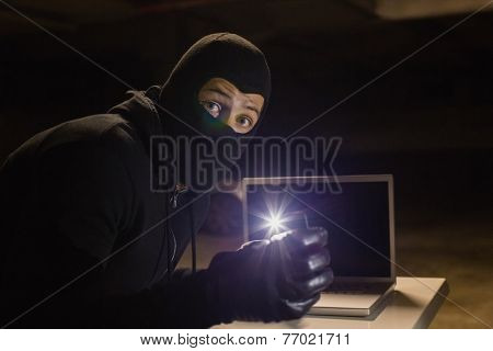 Robber looking at camera while making light with his phone on black background