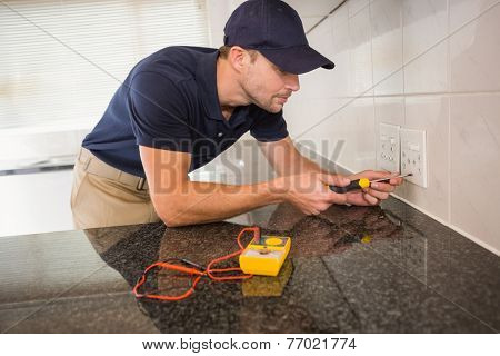 Electrician unscrewing face plate of plug socket in the kitchen