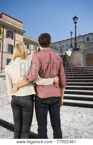 Young lovers looking at the spanish steps in Rome, sightseeing and visiting the highlights as tourists