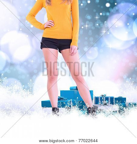 Lower half of woman in boots and shorts against light glowing dots on blue