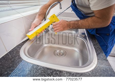 Plumber putting filling in between tiles in the kitchen