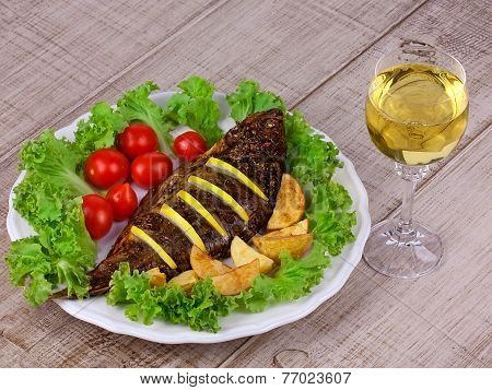 Whole grilled fish carp served with potatoes tomatoes cherry salad and lemon; glass of wine
