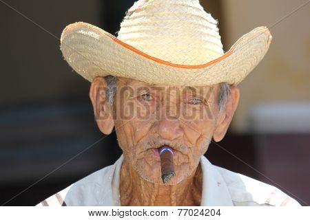 Old Man Smoking A Cuban Cigar.