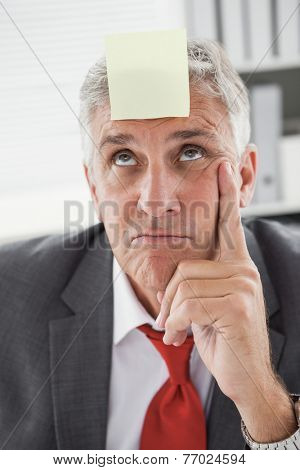 Confused businessman with sticky note on head in his office