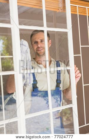 Handyman cleaning the window and smiling in a new house