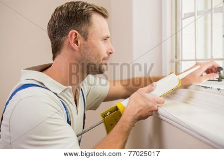 Man putting filling between window and wall in a new house
