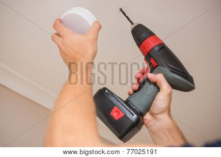 Handyman installing smoke detector with power tool on the ceiling