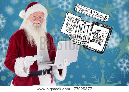 Santa pays with credit card on a laptop against snowflake wallpaper pattern