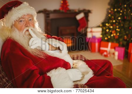 Santa claus keeping a secret at home in the living room