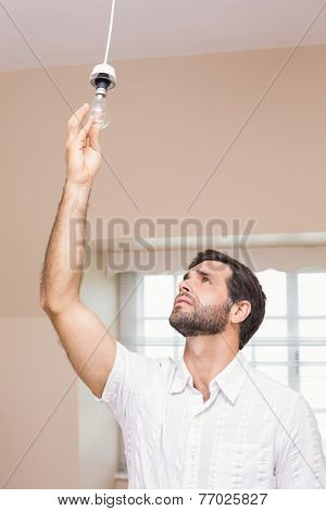 Man replacing the light bulb at home in the living room