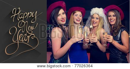 Laughing friends clinking champagne glasses at a hen night against classy new year greeting