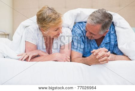 Senior couple smiling under the duvet at home in bedroom