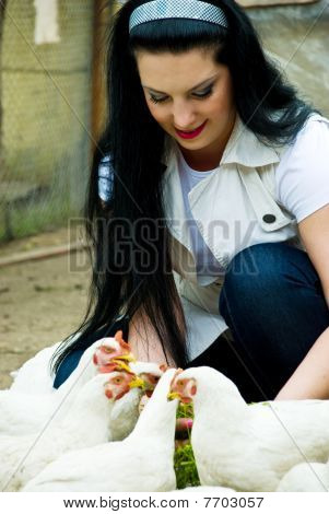 Smiling Woman Feeding Poultry