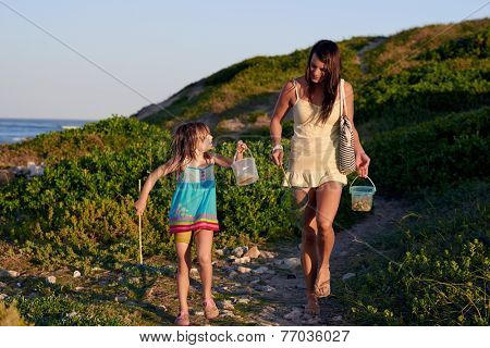Mom and daughter walking after going fishing at the bach on a summer afternoon