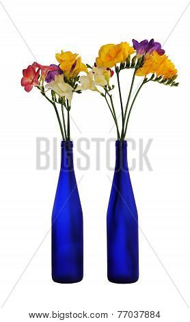 Two Blue Bottle With A Bunch Of Colorful Freesia