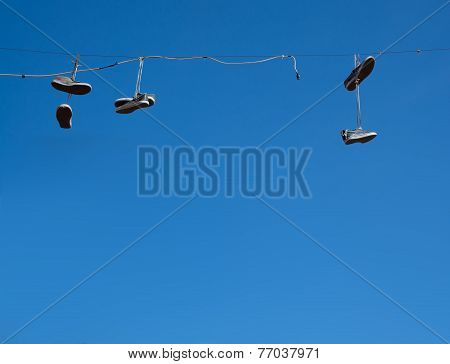 Shoes hanging blue sky