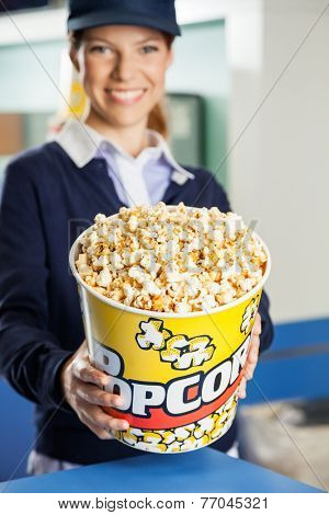 Portrait of happy female worker offering popcorn bucket at cinema concession stand