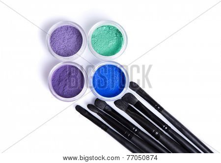 Mineral eye shadows and brushes, top view isolated on white background