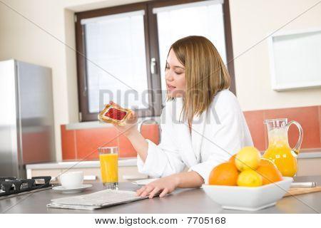 Breakfast - Smiling Woman Reading Newspaper In Kitchen