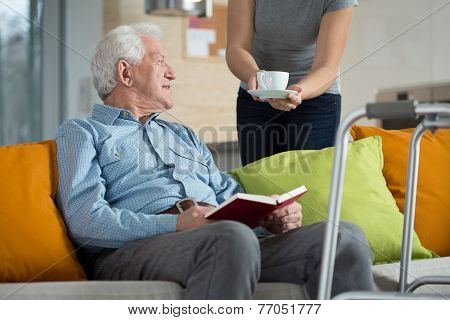Carer Giving Disabled Man Coffee