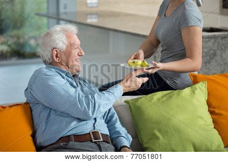 Daughter Giving Ill Grandpa Apple