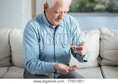 Ill Senior Man Taking Pill