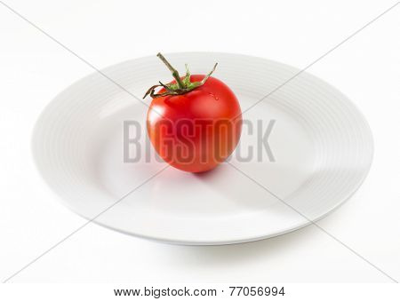 A single cherry tomato placed on a stark white plate.