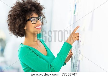 Afro woman looking at wall with adhesive notes