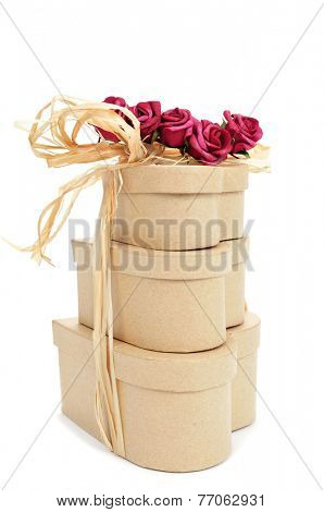 some heart-shaped gift boxes tied with natural raffia and topped with artificial red roses on a white background