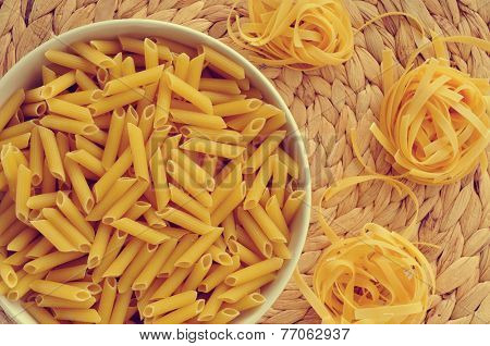 a bowl with uncooked penne rigate and some uncooked tagliatelle, with its characteristic nest shape