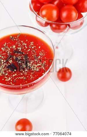 Tomato juice in glass goblet and fresh tomatoes on light wooden background