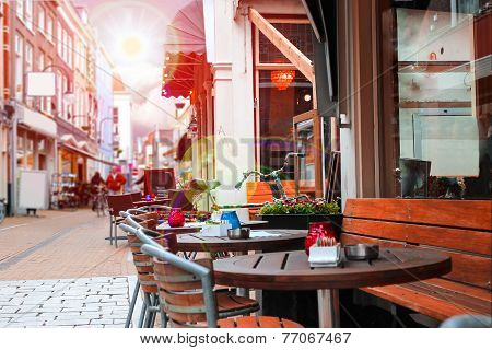 Urban Street With A Picturesque Cafe In Rays Sun