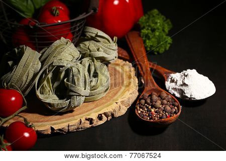 Composition of colorful pasta, fresh tomatoes, basil on wooden background