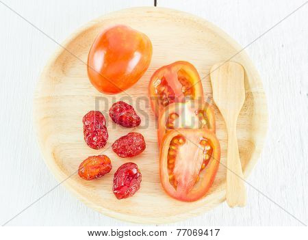 Fresh And Dried Tomatoes In Wood Plate On White Table